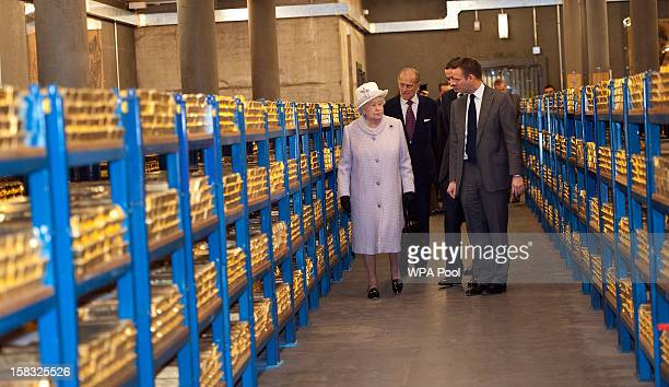 Queen Elizabeth II views stacks of gold as she visits the Bank of England with Prince Philip Duke of Edinburgh on December 13 2012 in London England...