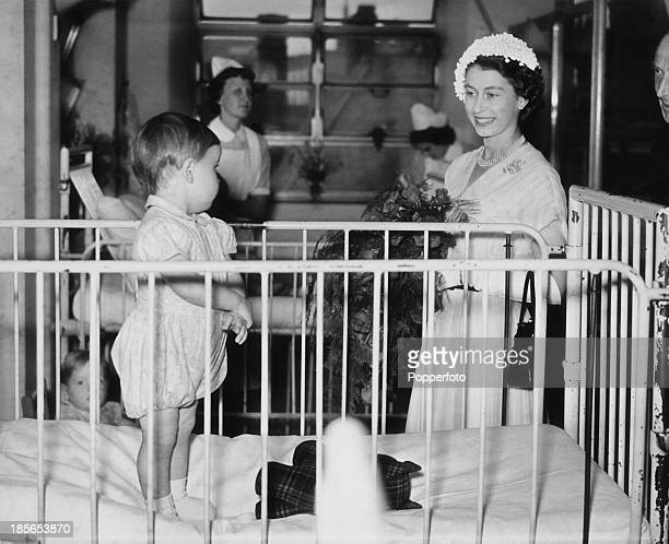 Queen Elizabeth II visiting a ward during a tour of Great Ormond Street Hospital for Sick Children 23rd July 1952 In the cot is 18 monthold patient...