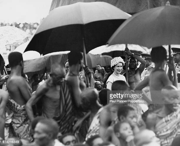Queen Elizabeth II walks amongst a retinue of Ashanti chiefs holding parasols and umbrellas at a durbar in Kumasi sports stadium in the city of...