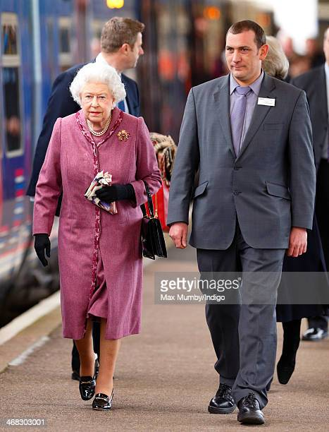 Queen Elizabeth II walks down the platform at King's Lynn Railway Station to board a train to London after spending the Christmas Holidays at...