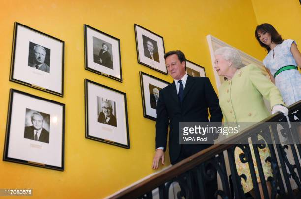 Queen Elizabeth II walks down the staircase in 10 Downing Street with Prime Minister David Cameron and his wife Samantha after they had lunch...