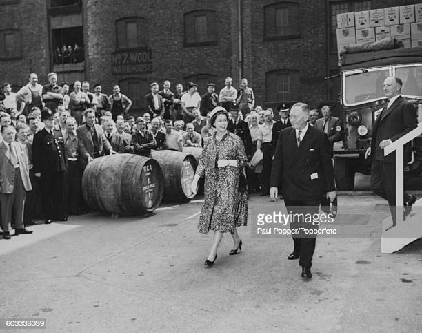 Queen Elizabeth II walks past a crowd of dockers and dock workers standing next to a number of large wine barrels as she arrives at the Crescent Wine...