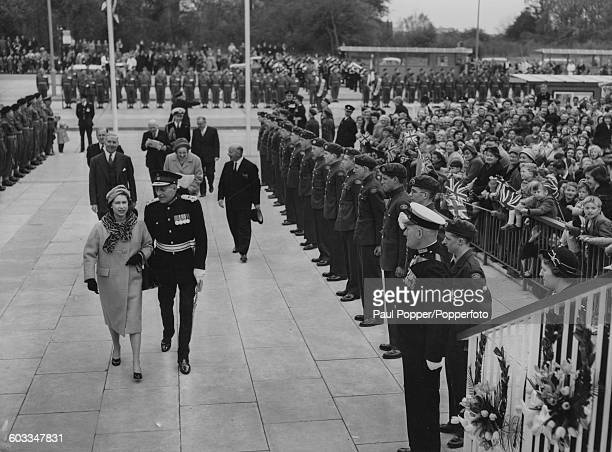 Queen Elizabeth II walks past a Guard of Honor as she arrives in the new town of Stevenage for the first time to unveil a commemorative plaque on the...