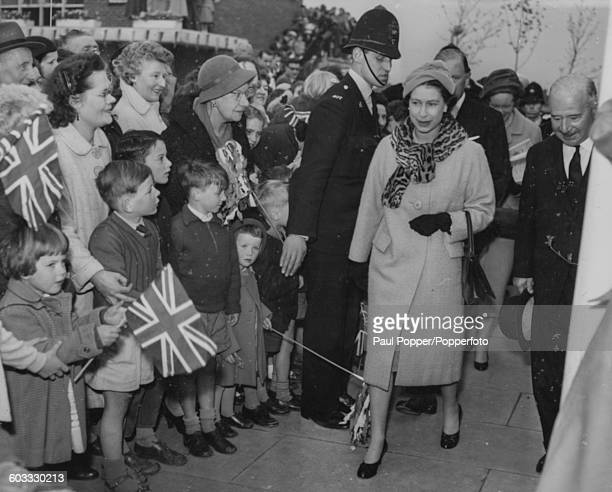 Queen Elizabeth II walks past crowds of people and children waving Union Jack flags as she arrives in the new town of Stevenage for the first time...