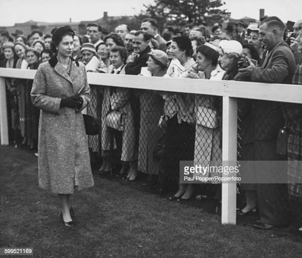 Queen Elizabeth II walks past crowds of spectators after visiting her horse 'High Velt' in the Parade Ring before the start of the St Leger at...