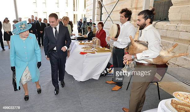 Queen Elizabeth II walks past Francesco Sultana as he plays the Zaqq which is similar to the bagpipes and made from the carcass of a dead goat during...