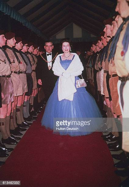 Queen Elizabeth II walks through a guard of honour formed by Boy Scouts during her visit to watch their 1962 gangshow at the Golder's Green Empire in...