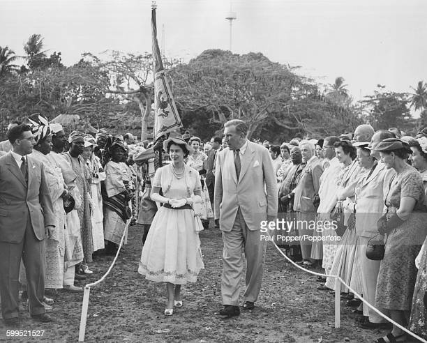 Queen Elizabeth II walks through the crowd as she arrives at a garden party held by the Governor General James Wilson Robertson and Lady Robertson in...