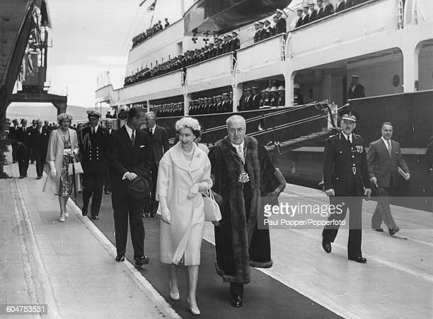 Queen Elizabeth II walks with George Steven the Lord Provost of Aberdeen followed by Prince Philip Duke of Edinburgh as they step off the Royal Yacht...