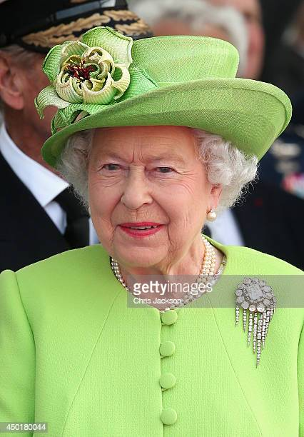 Queen Elizabeth II watches a Ceremony to Commemorate DDay 70 on Sword Beach on June 6 2014 in Ouistreham France Friday 6th June is the 70th...