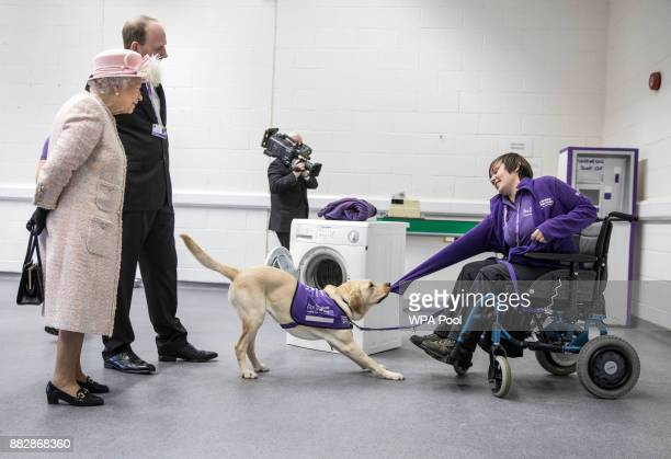 Queen Elizabeth II watches a demonstration by 'Hettie' the Labrador dog showing how she can help to undress a disabled owner as she tours the...