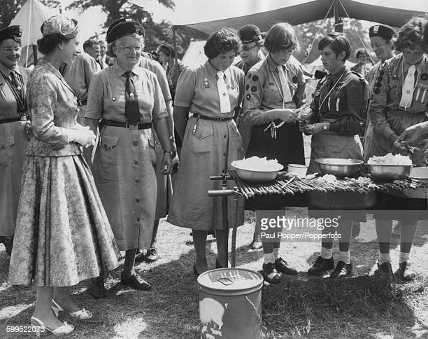 Queen Elizabeth II watches a group of girl guides carrying out cookhouse chores during a visit to the Guide World Camp in Windsor Great Park England...