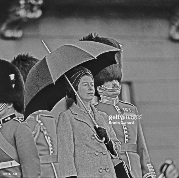 Queen Elizabeth II watches a march-past in the rain during the presentation of the colours to the 1st Battalion Welsh Guards in the grounds of...