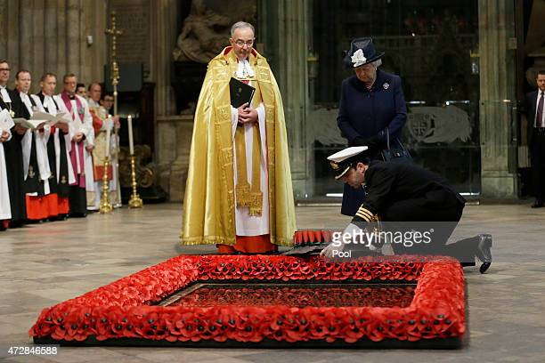 Queen Elizabeth II watches as a wreath is laid on her behalf at the Grave of the Unknown Warrior flanked by the Dean of Westminster John Hall at the...