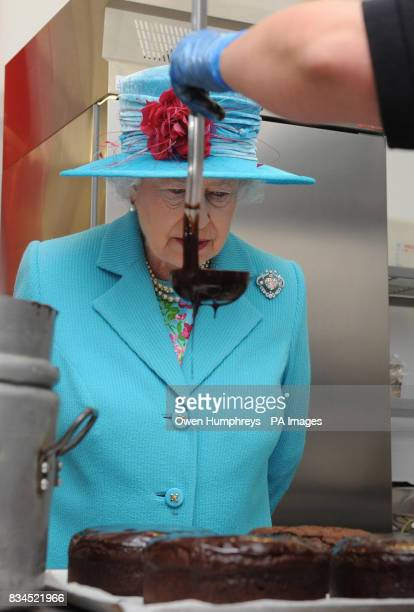 Queen Elizabeth II watches as Jo Hurst from the Pie Mill makes a chocolate cake during her visit to the Cumbrian Rural Enterprise Agency in Penrith...
