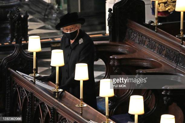 Queen Elizabeth II watches as pallbearers carry the coffin of Britain's Prince Philip, Duke of Edinburgh during his funeral inside St George's Chapel...