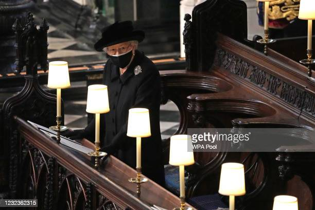 Queen Elizabeth II watches as pallbearers carry the coffin of Prince Philip, Duke Of Edinburgh into St George's Chapel by the pallbearers during the...