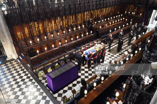 Queen Elizabeth II watches as pallbearers carry the coffin of the Prince Philip, Duke of Edinburgh, during his funeral at St George's Chapel at...
