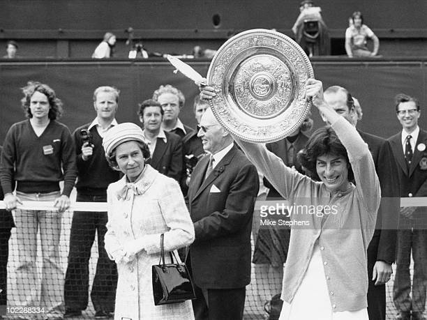 Queen Elizabeth II watches as the Women's Singles Champion, Virginia Wade from Britain, shows her trophy to the crowd on the centre court at...