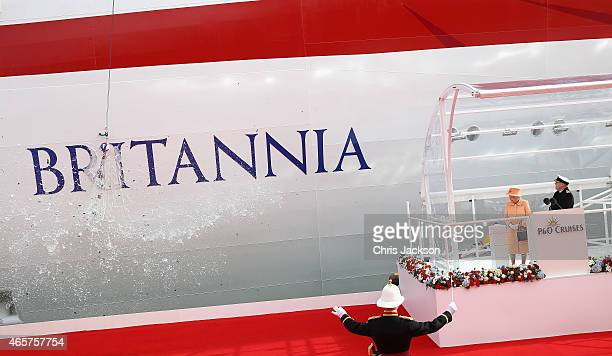 Queen Elizabeth II watches champagne smash on the hull of Britannia as she takes part in the naming ceremony for the PO Cruises vessel at Ocean...