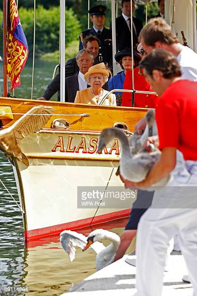 Queen Elizabeth II watches from the steam launch 'Alaska' as swan uppers place swans back into the river during a swan upping census on the River...