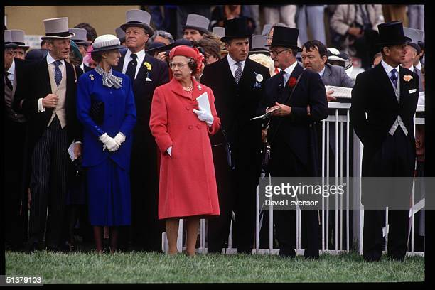 Queen Elizabeth II watches horses riding to the start of the Derby on June 7 1989 at Epsom Racecourse in Epsom Surrey To the Queen's left are the Hon...