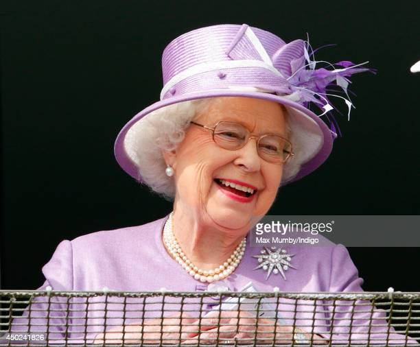 Queen Elizabeth II watches the racing as she attends Derby Day of the Investec Derby Festival at Epsom Racecourse on June 7 2014 in Epsom England