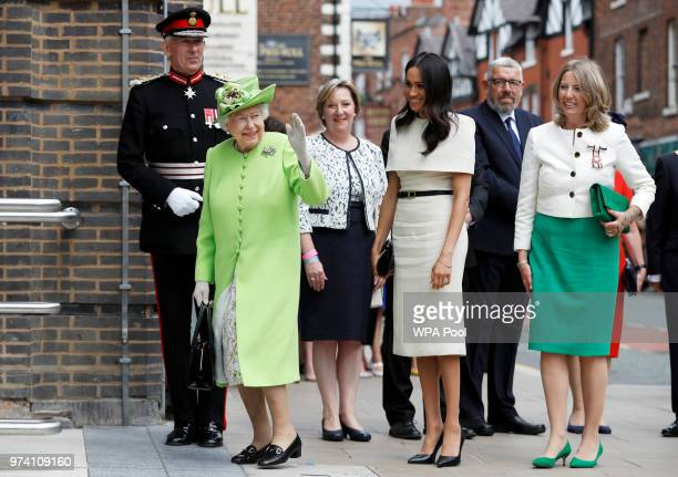 Queen Elizabeth II waves as Meghan Duchess of Sussex and her arrive for their visit to the Storyhouse on June 14 2018 in Chester England Meghan...