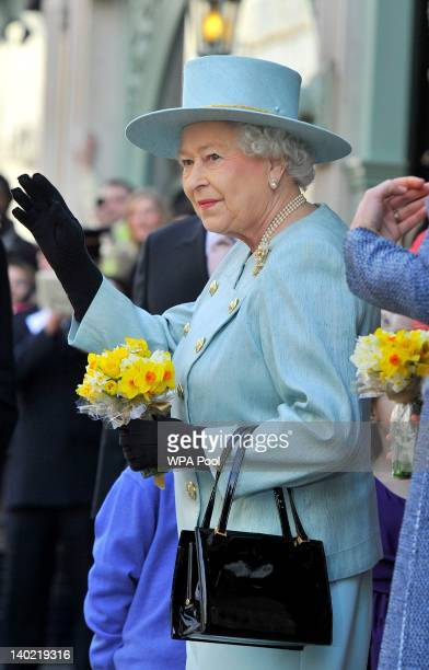 Queen Elizabeth II waves as she leaves Fortnum Mason store holding a posy of daffodils on St David's Day on March 1 2012 in London England Together...