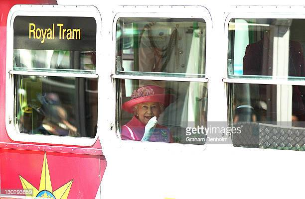 Queen Elizabeth II waves as she rides on the royal tram down St Kilda Road on October 26, 2011 in Melbourne, Australia. The Queen and Duke of...