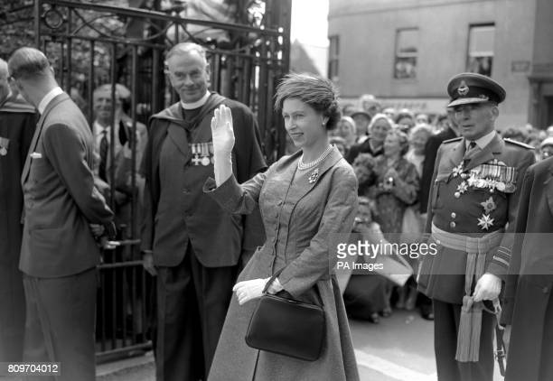 Queen Elizabeth II waves in response to the cheers of the pupils of Elizabeth College Guernsey during her Channel Islands tour