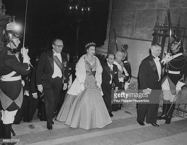Queen Elizabeth II, wearing a ball gown and tiara, arrives for a press reception and State Dinner at the Louvre with French Prime Minister Guy Mollet...