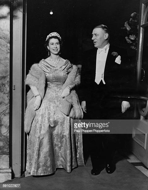 Queen Elizabeth II wearing a ball gown tiara diamond necklace and fur shawl as she attends the Royal Command Variety Performance with impresario Val...