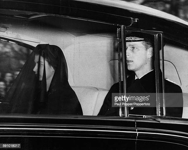 Queen Elizabeth II, wearing a black veil, sits in the back of a car with the Duke of Edinburgh after a funeral service for her grandmother, Queen...