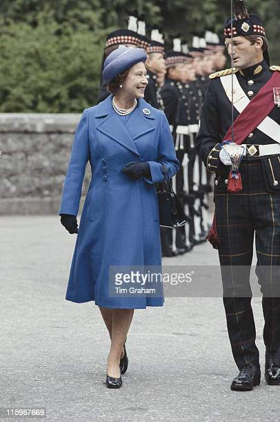 Queen Elizabeth II wearing a blue coat and matching hat in conversation with a soldier of the Scottish Royal Guards at Balmoral Castle on the...
