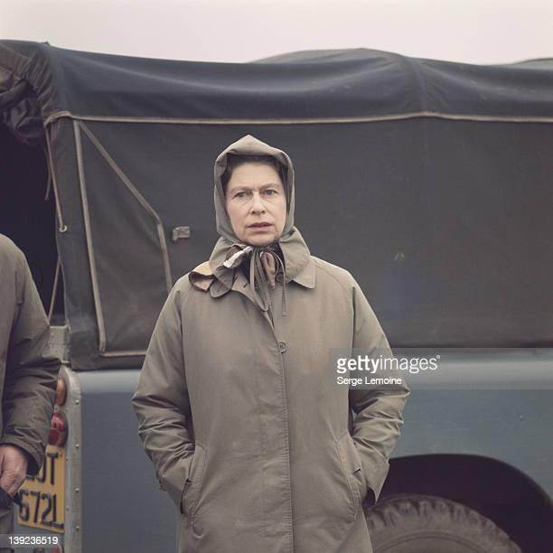 Queen Elizabeth II wearing a brown mackintosh at Windsor, 1975.
