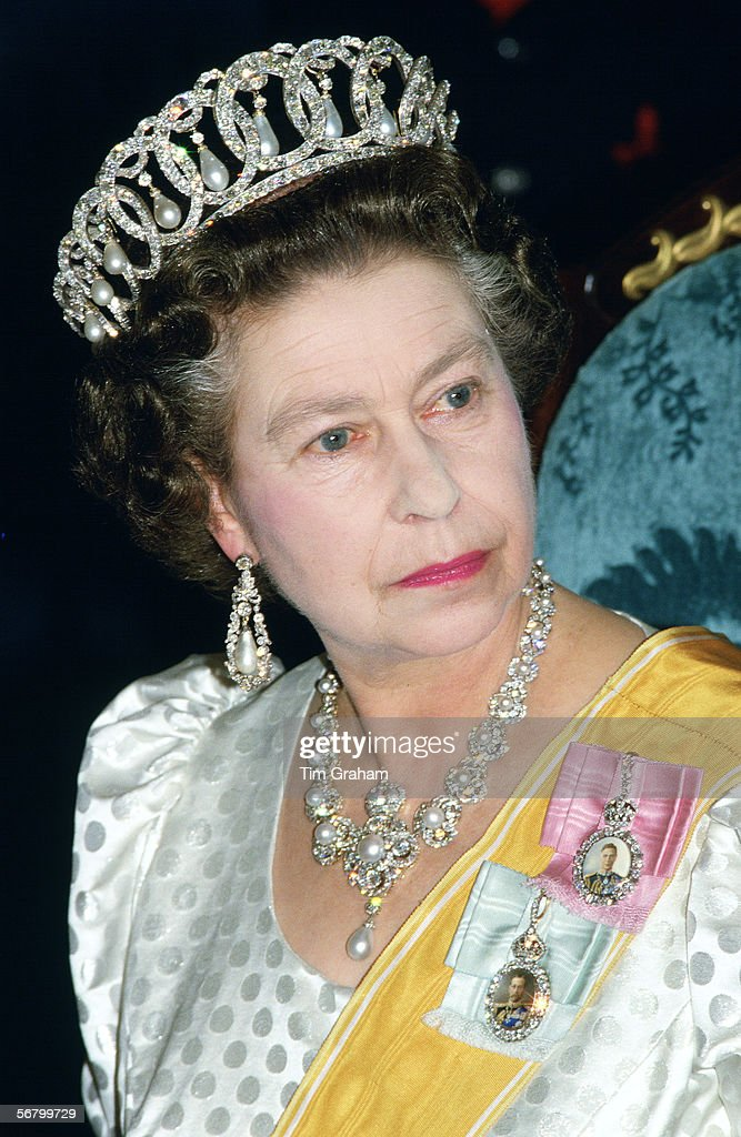 Queen Elizabeth II wearing a diamond and pearl circle tiara with the jubilee necklace at a state banquet during her official visit to Nepal.