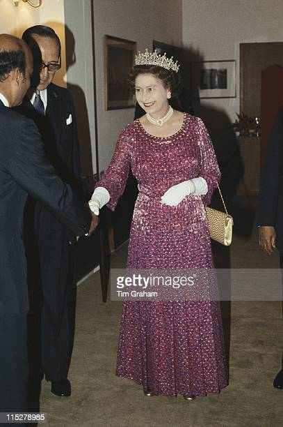Queen Elizabeth II wearing a fourstrand diamond and pearl choker with the 'Girl's of Great Britain and Ireland' tiara shaking hands with a guest at a...