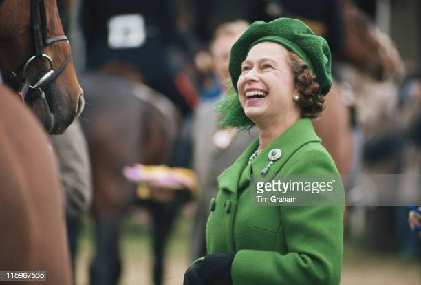 Queen Elizabeth II wearing a green coat and matching hat laughing as she attends the Royal Windsor Horse Show held at Home Park in Windsor Berkshire...