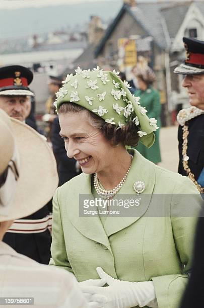 Queen Elizabeth II wearing a green jacket and beribboned hat circa 1973 The hat is by milliner Simone Mirman