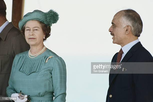 Queen Elizabeth II wearing a hat designed by Simone Mirman standing beside King Hussein of Jordan during a state visit to Jordan in March 1984