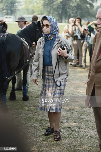 Queen Elizabeth II, wearing a headscarf and a tartan skirt, at the Royal Windsor Horse Show, held at Home Park in Windsor, Berkshire, England, Great...