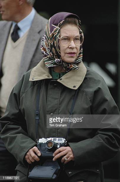 Queen Elizabeth II wearing a headscarf and green waxed jacket and holding a Leica camera at the Royal Windsor Horse Show held at Home Park in Windsor...