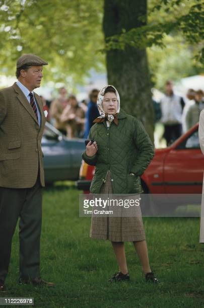 Queen Elizabeth II, wearing a headscarf, and Sir Michael Oswald, manager of the Royal Stud, attending the Royal Windsor Horse Show, held at Home Park...