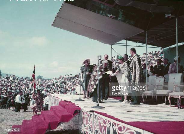 Queen Elizabeth II wearing a newly gifted Korowai Maori kiwi feather cloak at a Maori reception at Arawa Park Racecourse Rotorua during her...