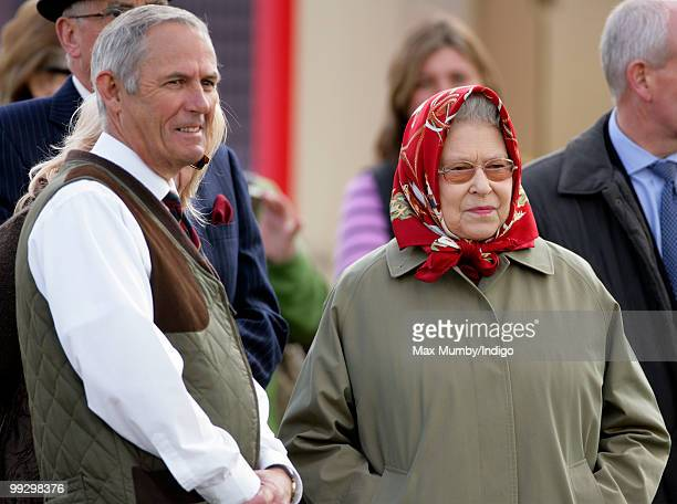 Queen Elizabeth II wearing a raincoat and headscarf and her stud groom Terry Pendry attend day 3 of the Royal Windsor Horse Show on May 14 2010 in...