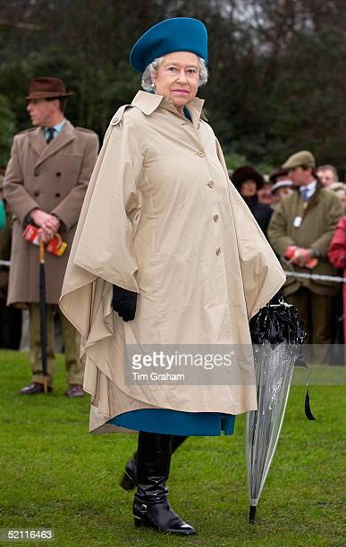 Queen Elizabeth II Wearing A Raincoat Cape And Carrying A Transparent Umbrella For Wet Weather At The Grand Military Race Meeting. The Queen Attended...