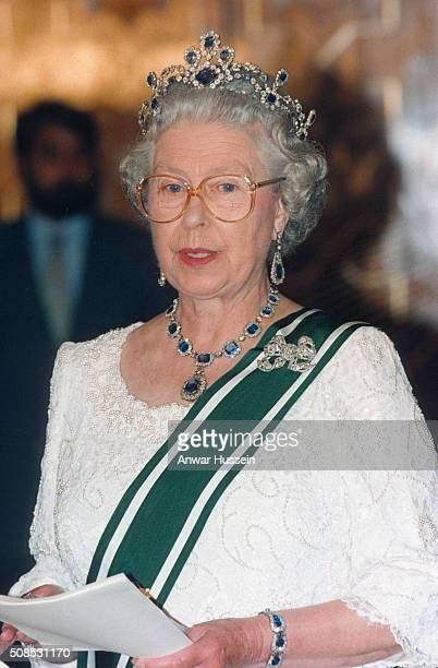 Queen Elizabeth II, wearing a sapphire and diamond tiara which she had made to match the cluster necklace and earrings which were a wedding present...