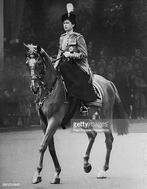 Queen Elizabeth II wearing a Scarlet Guards tunic, tricorn hat with osprey feather plume and Order of the Garter emblem, as she rides the police...