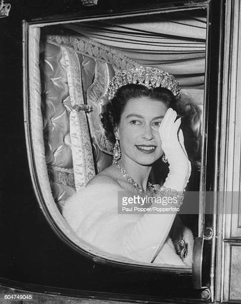 Queen Elizabeth II wearing a tiara diamonds pearls and a fur stole waves from the Danish State Coach as she arrives for a banquet at the...